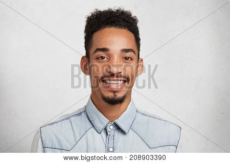 Indoor Shot Of Glad Young Bearded Man And Mustache, Wears Denim Shirt, Smiles Happily, Rejoice Succe