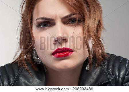 Suspicious look. Aggressive confident lady. Relationships problems, distrust in partner. Angry stylish female portrait on grey background closeup, suspicion concept