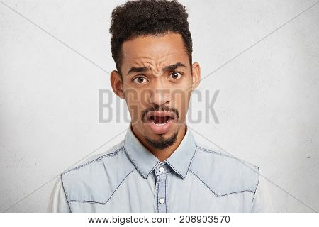 Negative Emotions And Body Language Concept. Unsatisfied Black Man Frowns Face And Looks With Opened