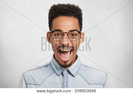 Emotional African American Male In Round Spectacles, Opens Mouth In Excitement, Exclaims Joyfully, B