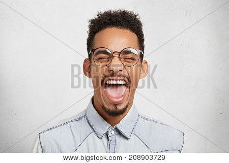 Yeah! Portrait Of Delightful Pleased Dark Skinned Male Closes Eyes And Opnes Mouth Widely, Shows Tee