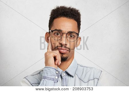 Confident Businessman Wears Spectacles, Keeps Finger On Chin As Listens Attentively Business Present