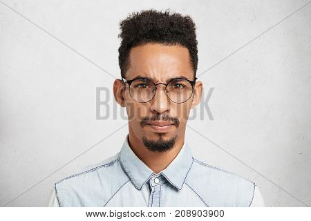 Indoor Portrait Of Displeased Discontent Upset Male Model With Trendy Hairdo, Mustache, Beard, Wears