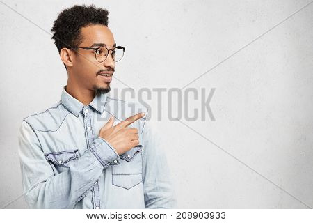 Sideways Portrait Of Intelligent Clever Young Man Has Mustache, Beard And Afro Hairstyle, Looks With