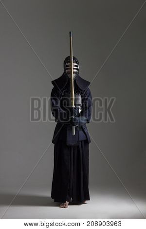 male in tradition kendo armor with bamboo sword. shot in studio on grey background