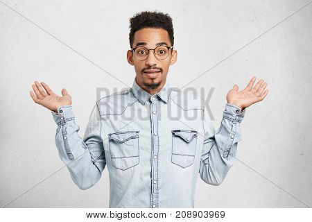Cropped Shot Of Fashionable Young Male Wears Denim Clothes And Glasses, Gestures With Hands, Says: W
