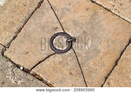 Chopped stone slab in the floor with an iron ring