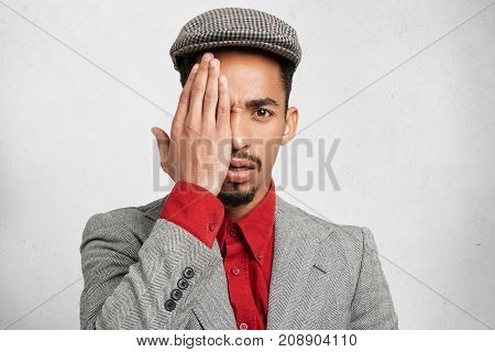 Portrait Of Attractive Male Wears Cap, Formal Red Shirt With Jacket, Covers Eye With Hand As Conceal