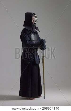 Portrait of man kendo fighter with bamboo sword in traditional armor. Shot in studio.