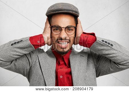 Stressful Bearded Man In Cap And Jacket, Covers Ears, Protects Himself From Noise, Doesn`t Want To H