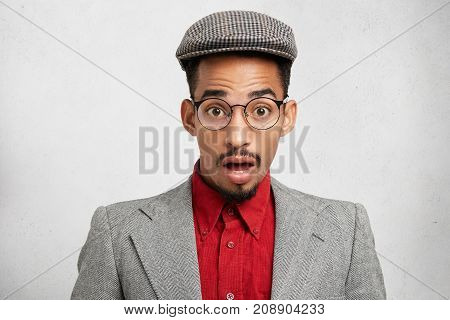 Indoor Picture Of Astonished Male Looks With Opened Mouth As Watches World News, Dressed Formally, I