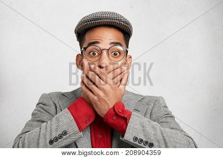 Portrait Of Surprised Worried Man In Spectacles Covers Mouth With Both Hands, Tries To Keeps Secret