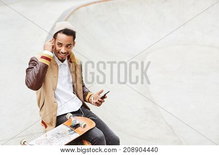 Skateboarding Concept. Stylish Carefree Teenager Does Skateboard, Rests After Active Day, Holds Mode