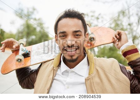 Carefree Mixed Race Male Sketaboarder Holds Skateboard Behind, Smiles Happily As Spends Unforgettabl