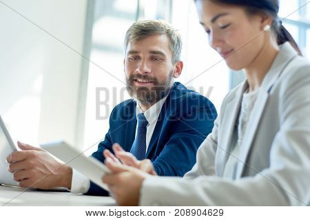 Waist-up portrait of handsome bearded entrepreneur sitting next to his female colleague at boardroom and looking at touchscreen of her digital tablet with interest