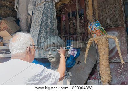 KUMARTULI KOLKATA INDIA - OCTOBER 10 2014 - Artist preparing clay idol of a soldier.