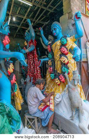 KUMARTULI KOLKATA INDIA - OCTOBER 10 2014 - Artist preparing clay idol to be worshipped as Goddess Kali during Kali Puja Hindu festival of Deepavali or Diwali. Celebtated all over India.