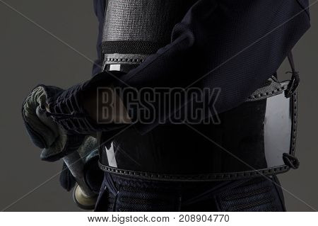 close up of a kendo fighter in traditional kendo armor with bamboo sword preparing for the fight. shot in studio on grey background