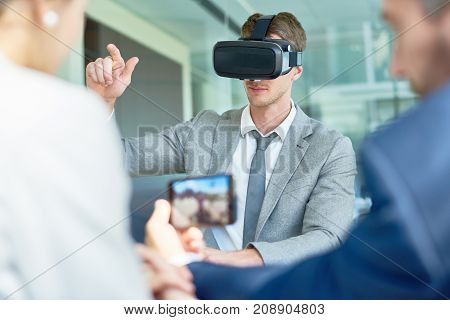 Young beaded entrepreneur using VR headset while having start-up project discussing with colleagues at spacious boardroom
