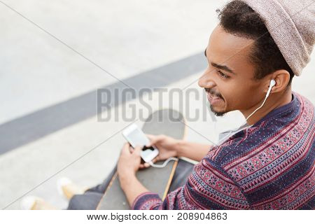 Fashionable Dark Skinned Youngster Wears Trendy Hat And Shirt, Enjoys Favourite Genre Of Music, Uses