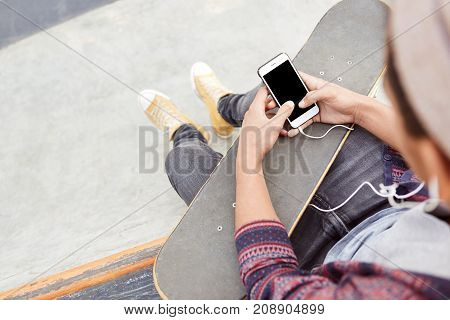 Cropped Shot Of Fashionable Teenager Wears Sport Shoes And Jeans, Holds Skateboard, Uses Modern Smar