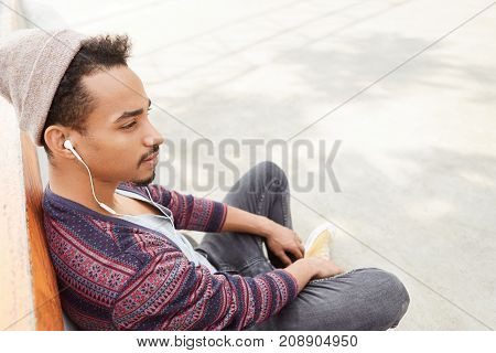 Pensive Bearded Hipstre Guy Wears Trendy Hat, Sits Crossed Legs On Ground, Listens To Sad Melodies A