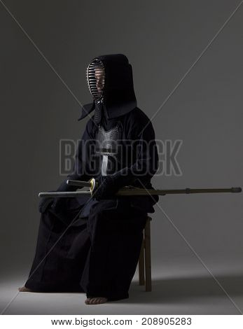 Portrait of man kendo fighter with bamboo sword in traditional armor sitting on the chair. Shot in studio.