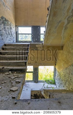 Stair from the old factory. Abandoned factory industrial interior. Inside the ruins of an old factory in Romania of a Communist Era. Step inside of abandoned old factory in eastern Europe.