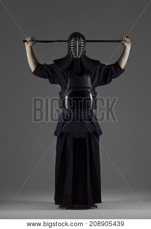 portrait of male in tradition kendo armor putting his helmet and preparing for the fight. shot in studio on grey background