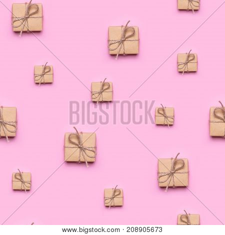 Seamless pattern made of gift wrapped in kraft paper on a pink background. View from above, flat lay design.
