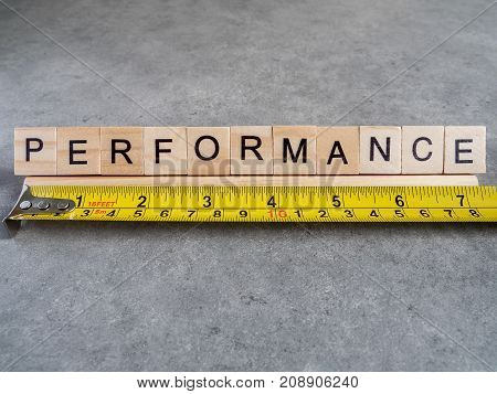Word spelling Performance and measuring tape on bare cement or concrete wall background