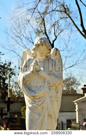 Figure of an angel with wings in the cemetery against the sky.