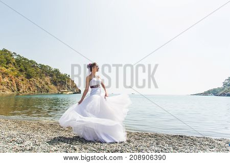 Beautiful young bride standing on the beach near the sea.