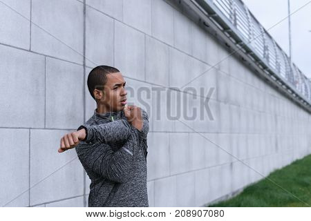 People health wellbeing motivation strenght sports and fitness concept. Candid shot of attractive self confident young Afro American sportsman doing physical exercises outdoors stretching arms poster
