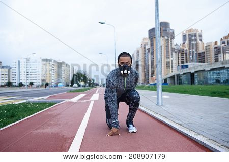 Ready steady go. Outdoor shot of stylish sportsman crouching in ready position going to run on running track wearing trendy sports outfit and training mask to stay stronger during jogging exercise
