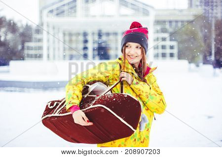 A woman with a bag of a child standing on the street in winter