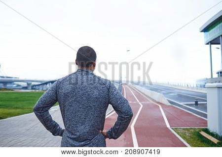 Back view of unrecognizable young dark-skinned male athlete standing on racetrack at stadium keeping hands on his waist while relaxing after running workout preparing for sprint or marathon