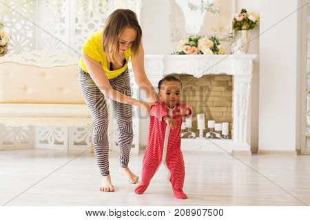 Cute little baby learning to walk, mom is holding his hands.