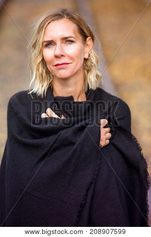 portrait of beautiful blond woman standing outside and smiling at camera