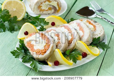 Homemade mackerel roll with carrots and eggs in gelatin. Sliced pieces of rolls are served with lemon cranberries and parsley. Festive snack. Mackerel roll lemon and parsley on green wooden table