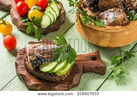 Canned food from mackerel of homemade preparation in wooden bowl. Served with fresh vegetables and herbs. Tomatoes and cucumbers on wooden board