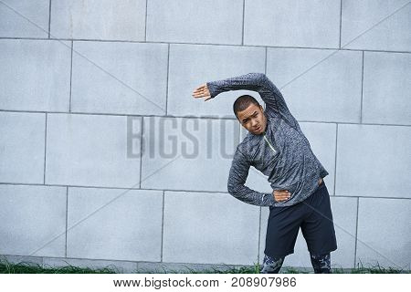 Sports activity health and fitness concept. Fit young African male athlete doing side bends with hand on his waist standing against grey brick wall background with copy space for your content