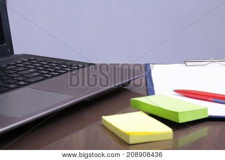 Office workplace with laptop, smart phone on table.