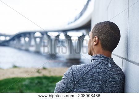 Rear view of thoughtful African American male runner in stylish sports jacket leaning on wall outdoors looking into distance at sea relaxing mind or meditating after running exercise in the morning