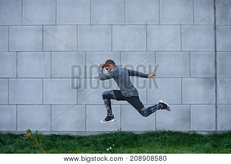 Sideview summer portrait of strong determined young dark-skinned sportsman exercising outdoors jumping high against brick wall background with copy space for your information. Freeze action shot