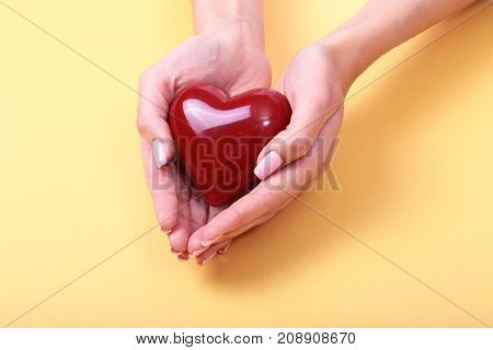 Female hands giving red heart, isolated on gold background.