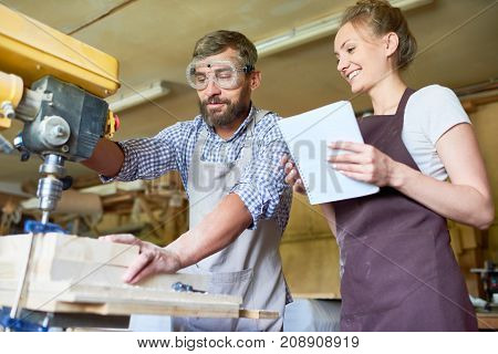 Portrait of bearded carpenter showing operating process of drilling machine to his female assistant in woodworking shop