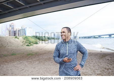 Handsome positive young Afro American male runner with joyful smile enjoying running workout outdoors on empty beach listening to dynamic tracks with earphones using online music app on mobile