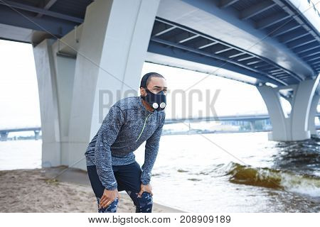 Lifestyle picture of tired young African American male runner in training mask resting having break during evening running workout on city beach catching his breath with hands on his knees