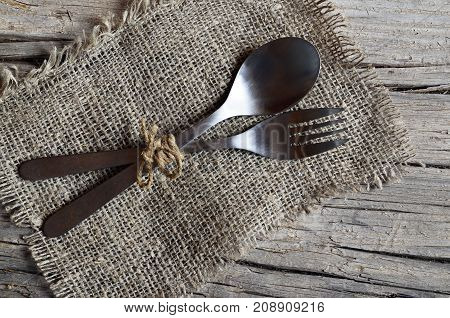 Cutlery set:fork and spoon on burlap cloth on rustic wooden table.Cutlery on old wooden background.Can be used as background menu for restaurant.